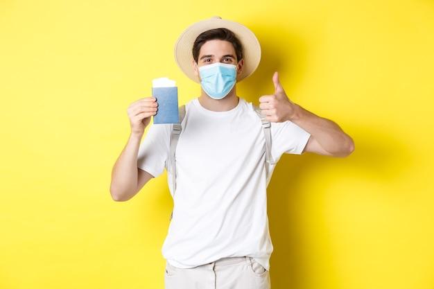 Covid-19, 관광 및 전염병의 개념. 의료 마스크 보여주는 여권, 코로나 바이러스 동안 휴가를가는 행복 한 남성 관광, 가입 엄지 손가락, 노란색 배경.