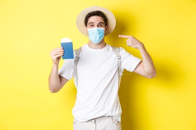 Covid-19の概念、観光とパンデミック。パスポートを示す男性観光客、コロナウイルスからの保護のための医療マスク、黄色の背景で旅行
