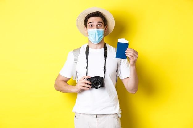 Covid-19の概念、旅行および検疫。カメラを持って幸せな男の観光客、パスポートと休暇のチケットを示し、パンデミック、黄色の背景の間に旅行に行きます。