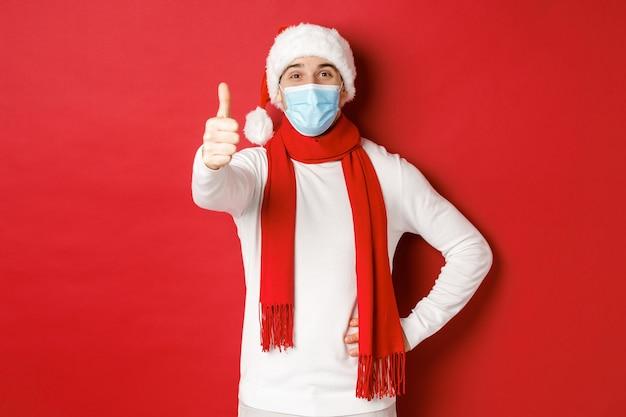 전염병 동안 covid 크리스마스와 휴일의 개념은 의료 마스크와 사에서 쾌활한 잘 생긴 남자 ...