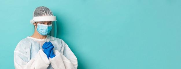 Covid 전염병의 개념과 개인 보호 장비를 갖춘 희망적인 여성 의사의 격리 근접 촬영...