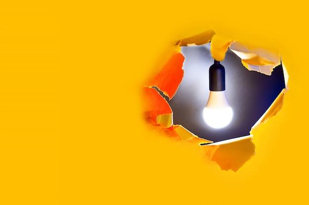 創造的なアイデアの概念。黄色い紙の穴に電球が光る