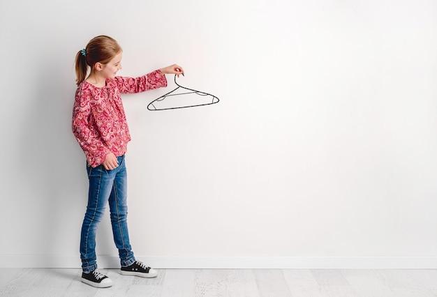 Концепция творческого ума и фантазии детской женщины, держащей тремпель изолированы