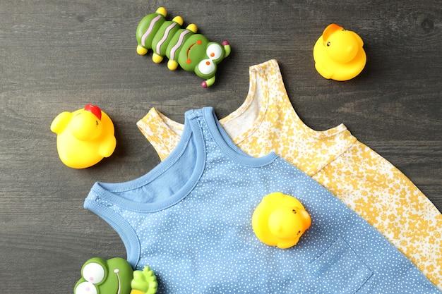 Концепция милой детской одежды на темном текстурированном фоне.