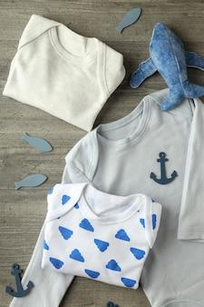 Концепция милой детской одежды на сером текстурированном фоне.