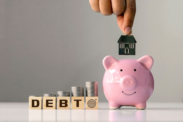 부채 및 재정 목표의 개념. 부채와 손을 핑크 돼지 저축에 집 모델을 들고 표시 된 누적 된 나무 블록에 동전.