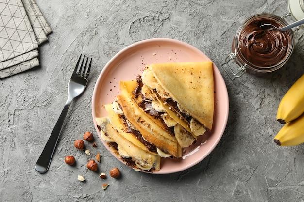 Концепция вкусного завтрака с блинчиками с шоколадной пастой, бананом и орехами на сером фоне