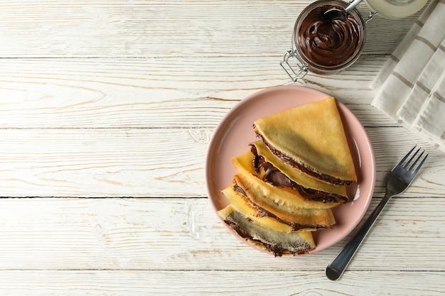 Концепция вкусного завтрака с блинчиками с шоколадной пастой на белом деревянном фоне