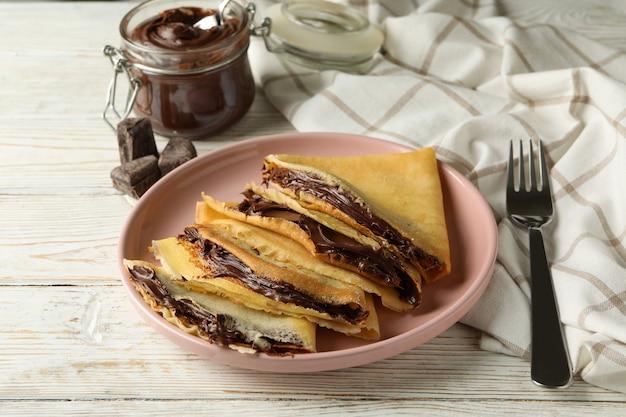 흰색 나무 표면에 초콜릿 페이스트와 크레페와 함께 맛있는 아침 식사의 개념