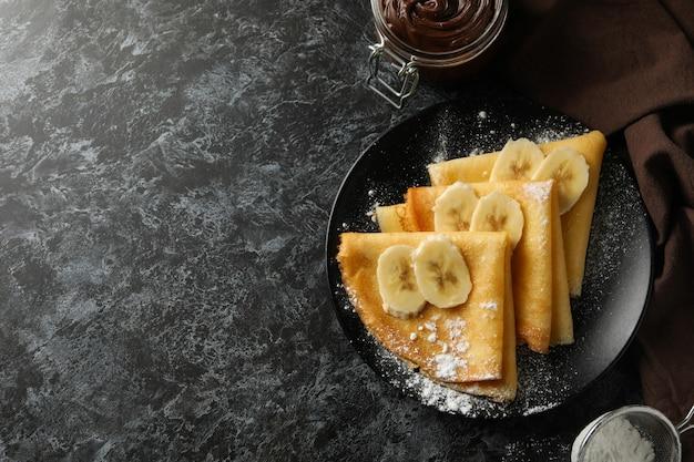 검은 스모키 배경에 설탕 가루와 바나나 크레페와 함께 맛있는 아침 식사의 개념