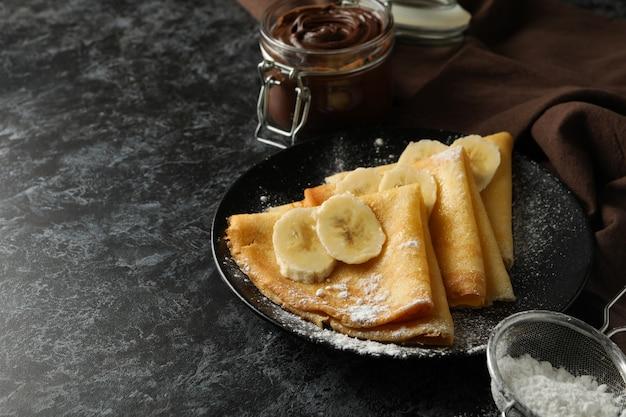 검은 스모키 표면에 설탕 가루와 바나나 크레페와 함께 맛있는 아침 식사의 개념