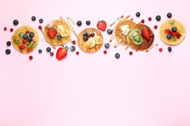 ピンクの背景にパンケーキを添えたおいしいデザートのコンセプト