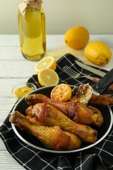 Концепция вкусной еды с кастрюлей жареных куриных голеней на белом деревянном столе