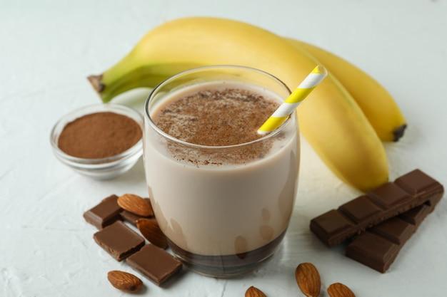 Концепция вкусной еды с шоколадным молочным коктейлем и бананом на белом текстурированном столе
