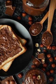 Концепция вкусной еды с шоколадной пастой на черном дымчатом фоне