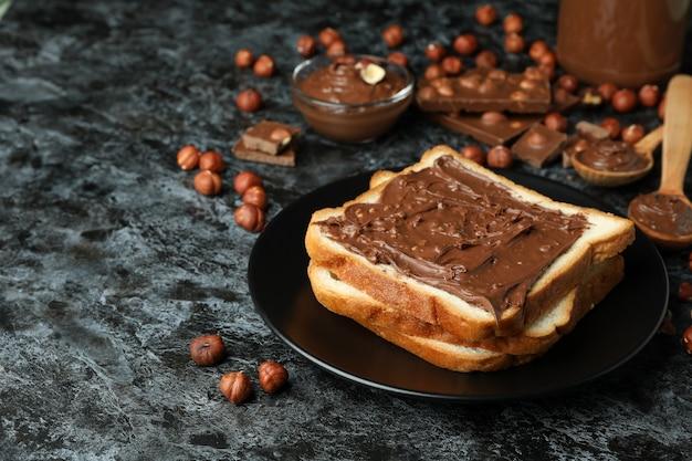 黒のスモーキーな背景にチョコレートペーストとおいしい料理のコンセプト