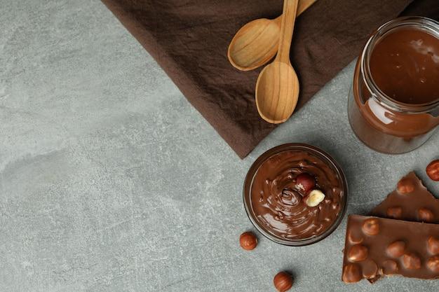 Концепция вкусной еды с шоколадной пастой на сером текстурированном столе