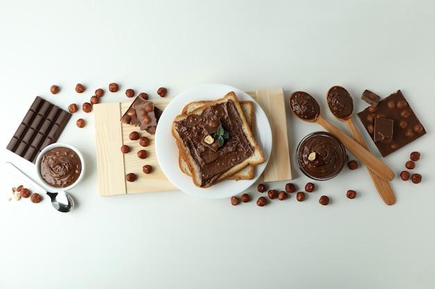 白い背景の上のチョコレートペーストとおいしい料理の概念