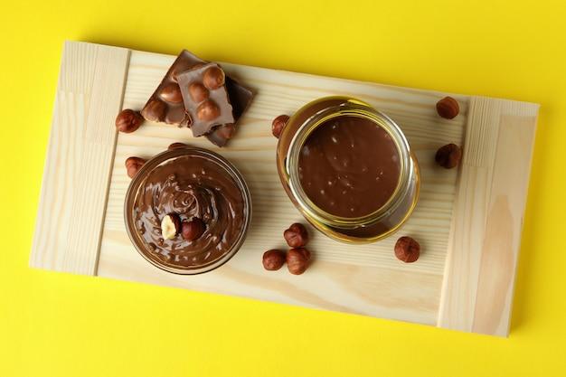 Концепция вкусной еды с шоколадной пастой на желтом фоне
