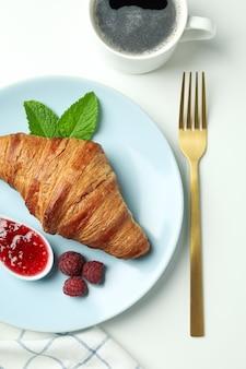 Концепция вкусной еды с круассаном с малиновым джемом на белом фоне