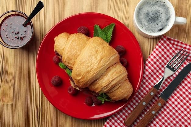 Концепция вкусной еды с круассаном с малиновым вареньем на деревянном фоне