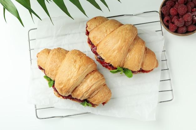Концепция вкусной еды с круассанами с малиновым джемом на белом фоне
