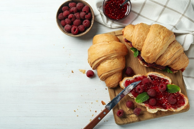Концепция вкусной еды с круассанами с малиновым джемом на белом деревянном фоне