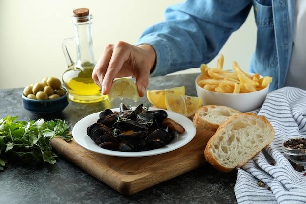 검은 스모키 테이블에 홍합을 넣은 맛있는 음식의 개념