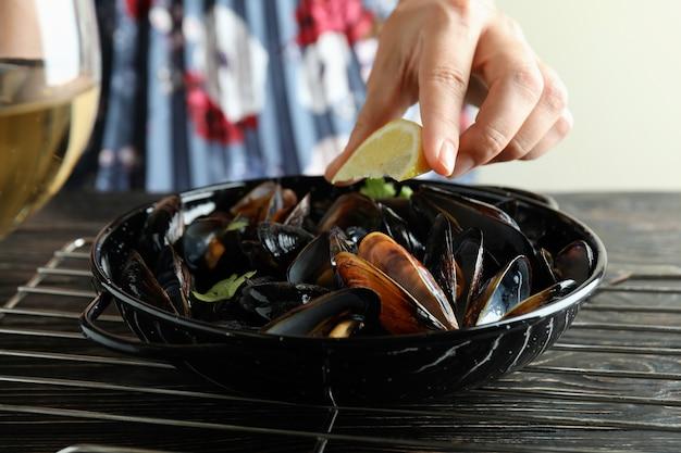 나무 테이블에 홍합을 넣은 맛있는 음식의 개념