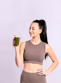 해독, 건강한 식단 및 피트니스의 개념. 녹색 스무디와 유리를 들고 젊은 여자.