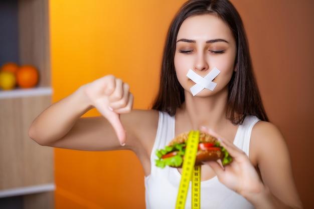Концепция диеты милая женщина с загерметизированным ртом держит жирный бургер