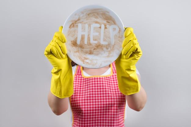 食器洗い中の難しさの概念。家で一生懸命働いて苦しんでいる機嫌が悪い妻の感触のクローズアップ写真は、白い食器類の孤立した灰色の背景で顔を覆って隠れています