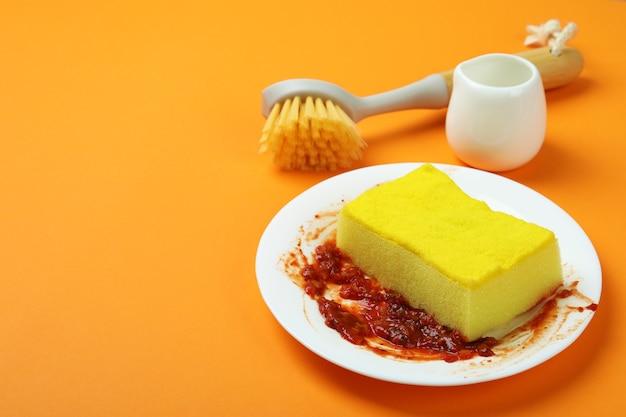 Концепция грязной посуды на оранжевом фоне