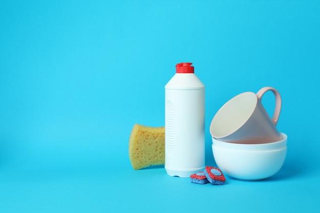 Концепция аксессуаров для мытья посуды на синем фоне