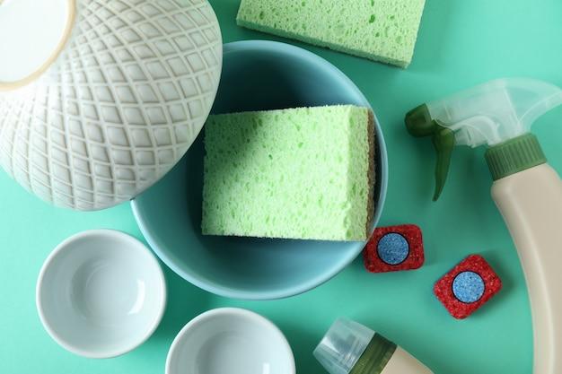 Концепция аксессуаров для мытья посуды на фоне мяты