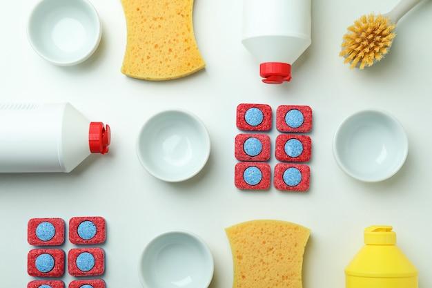 Концепция аксессуаров для мытья посуды на белом фоне