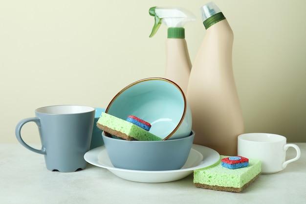 Концепция аксессуаров для мытья посуды на белом текстурированном столе