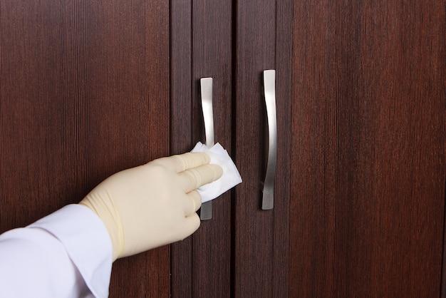 Концепция дезинфекции поверхностей от бактерий или вирусов, подоконник, рука с перчаткой, чистка дверной ручки с дезинфицирующим средством, влажная салфетка, коронавирус, covid 19
