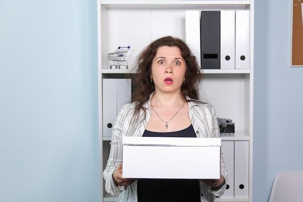 Концепция увольнения с работы. ошеломленная женщина с картонной коробкой со своими канцтоварами, девушка была уволена с работы.