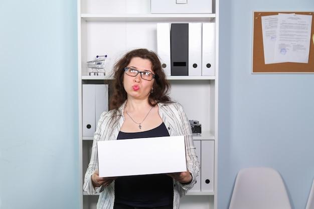 解雇の概念。段ボール箱と段ボール箱を持った驚く女性、彼女は仕事から解雇された。