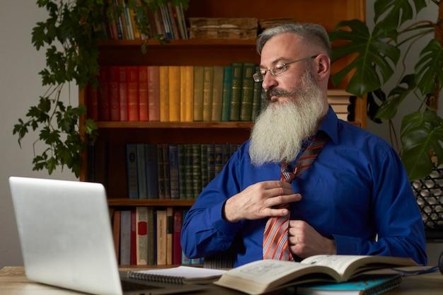 Концепция дистанционного обучения. учитель надевает галстук и готовится к онлайн-уроку. зрелый бородатый мужчина готовится к онлайн-тренировкам.