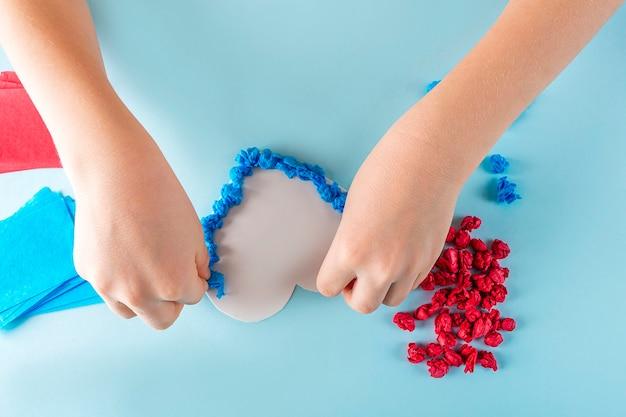 Diy와 아이의 창의력의 개념. 어린이 손에 색종이 조각을 구겨집니다. 발렌타인 데이 공예.