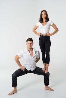 Концепция доминирующих женщин на мужчине в отношениях с женщиной, стоящей на колене мужчины с белым фоном
