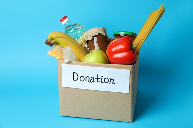 青い背景の募金箱で寄付の概念