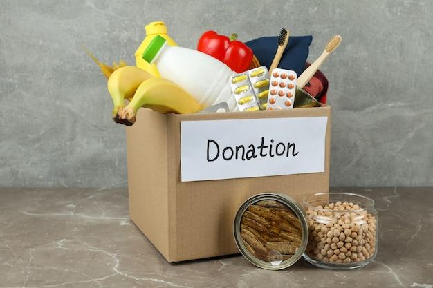 灰色のテクスチャテーブルの募金箱で寄付の概念