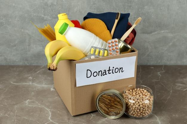 Концепция пожертвования с коробкой для пожертвований на сером текстурированном столе