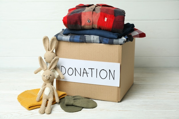 Концепция пожертвовать с коробкой для пожертвований на белом деревянном столе