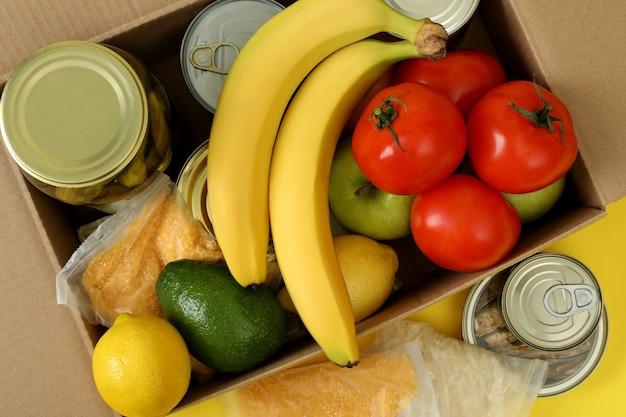黄色の背景に募金箱で寄付の概念