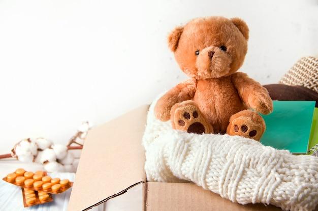寄付の概念、ケアを送る。箱の中には、物、文房具、ビタミン、おもちゃがあります
