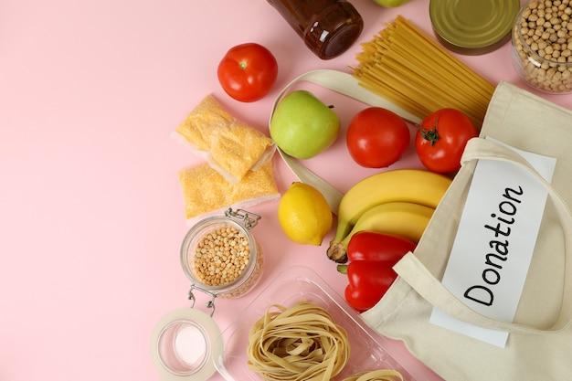 ピンクの背景に食べ物と寄付の概念